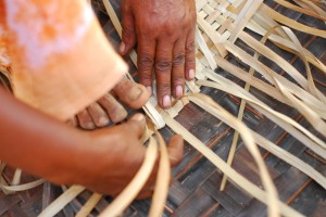 A lady demonstrating the art of weaving with palm fronds